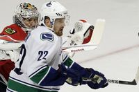 Vancouver Canucks left wing Daniel Sedin (22) and Chicago Blackhawks goalie Corey Crawford keep their eyes on the puck during the third period in Game 6 of an NHL hockey Stanley Cup playoffs first-round series Sunday, April 24, 2011, in Chicago.