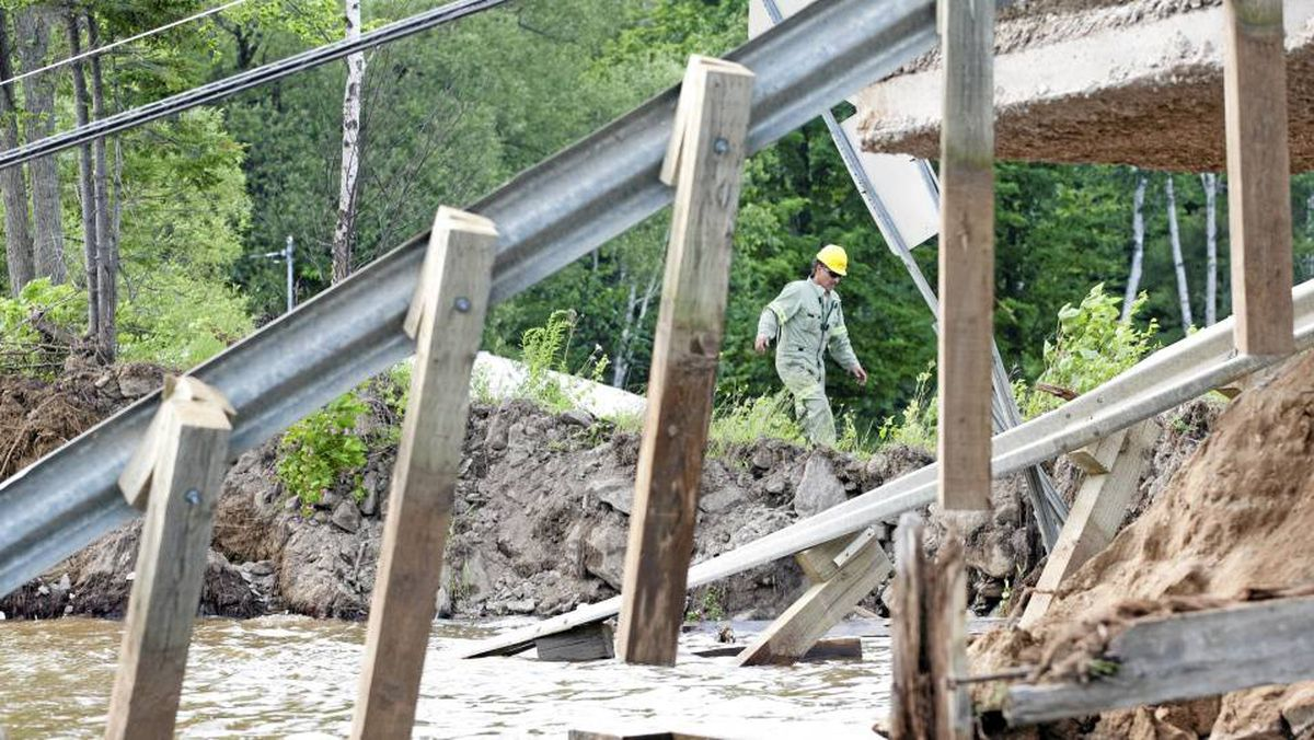 A Hydro Quebec worker navigates a causeway where a section of road collapsed following an earthquake in Bowman, Quebec Wednesday June 23, 2010.