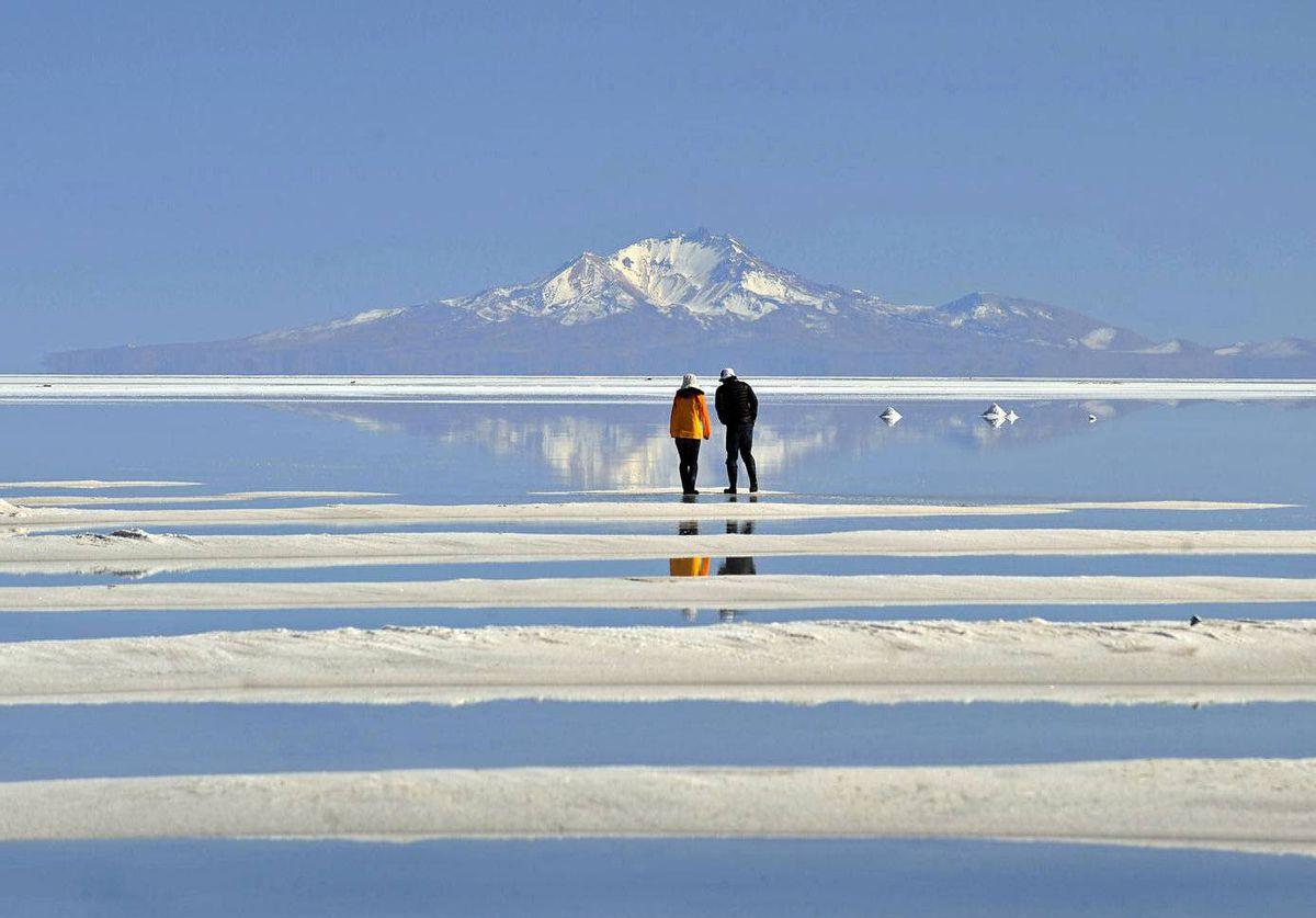 Japanese tourists walk on the world's largest salt flat at Uyuni, 550 km southwest of La Paz, Bolivia.
