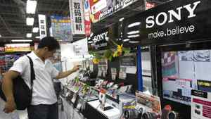 A shopper takes a look at Sony's digital camera at an electronics retail store in Tokyo, Japan, Thursday, July 28, 2011.