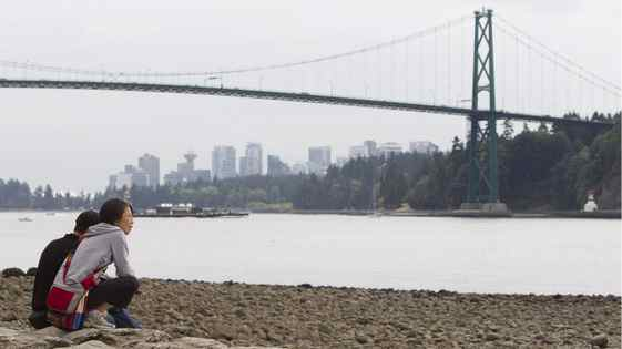 The Lions Gate Bridge can be seen in the background as a couple sit on the beach in West Vancouver, Tuesday, Sept. 13, 2011.