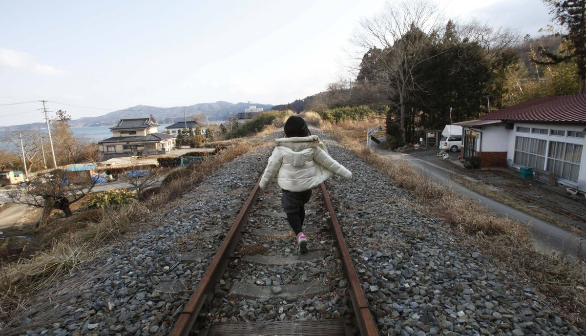 Manami Watanabe, 11, walks along a railtrack which is no longer used since last year's tsunami in Minamisanriku town, in Miyagi prefecture, northeastern Japan February 24, 2012. Watanabe's mother, grandmother and family home were swept away by the Tsunami on March 11, 2011.