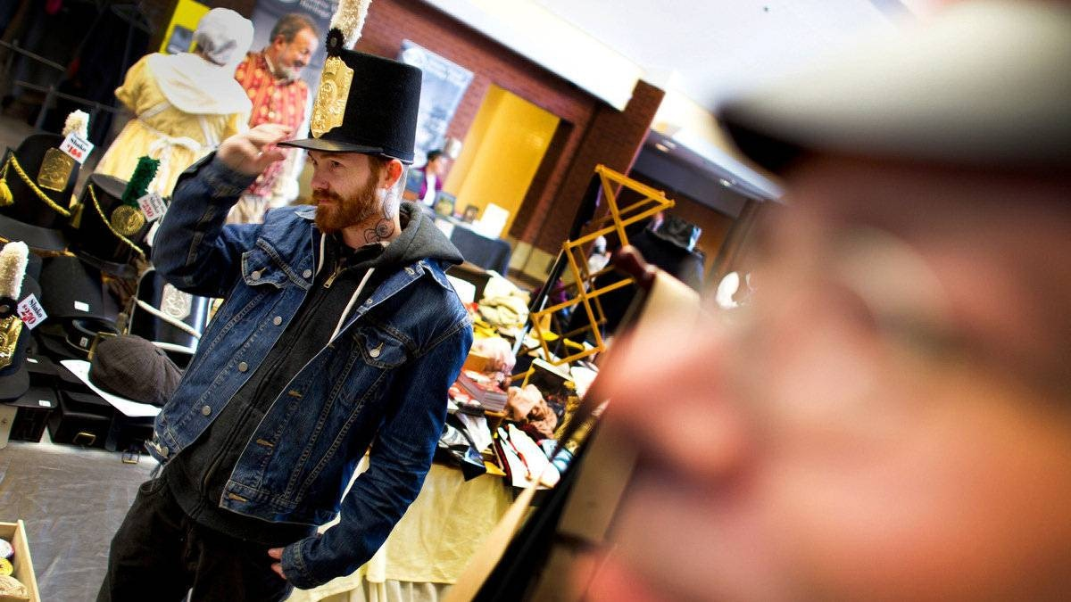 Bobby Taylor, 31, a tattoo artist from Welland, Ont., who is just getting into re-enacting with the 49th Regiment Foot, tries on a shako hat at the booth of P.C.E. Leather Works, run by Philip Charles Edwards. Mr. Taylor bought the shako as well as a number of other items to complete his 1812 soldier's attire.
