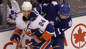 New York Islander Radek Martinek and Toronto Maple Leaf Fredrik Sjostrom get tangled up as the fight for the puck during first period NHL action Oct 18, 2010 in Toronto. (Moe Doiron/The Globe and Mail)