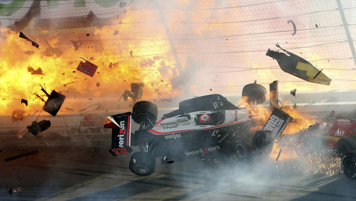 The race car of driver Will Power hits the wall as flames from British driver Dan Wheldon'sæcar burst (at left) during the IZOD IndyCar World Championship race at the Las Vegas Motor Speedway in Las Vegas, Nevada October 16, 2011. Wheldon died from injuries sustained in an horrific crash at the Las Vegas Motor Speedway on Sunday, race organizers said. The 33-year-old Englishman, who lived in Florida, was involved in a multi-car accident 13 laps into the Las Vegas Indy 300 which sent his vehicle flying. REUTERS/Barry Ambrose