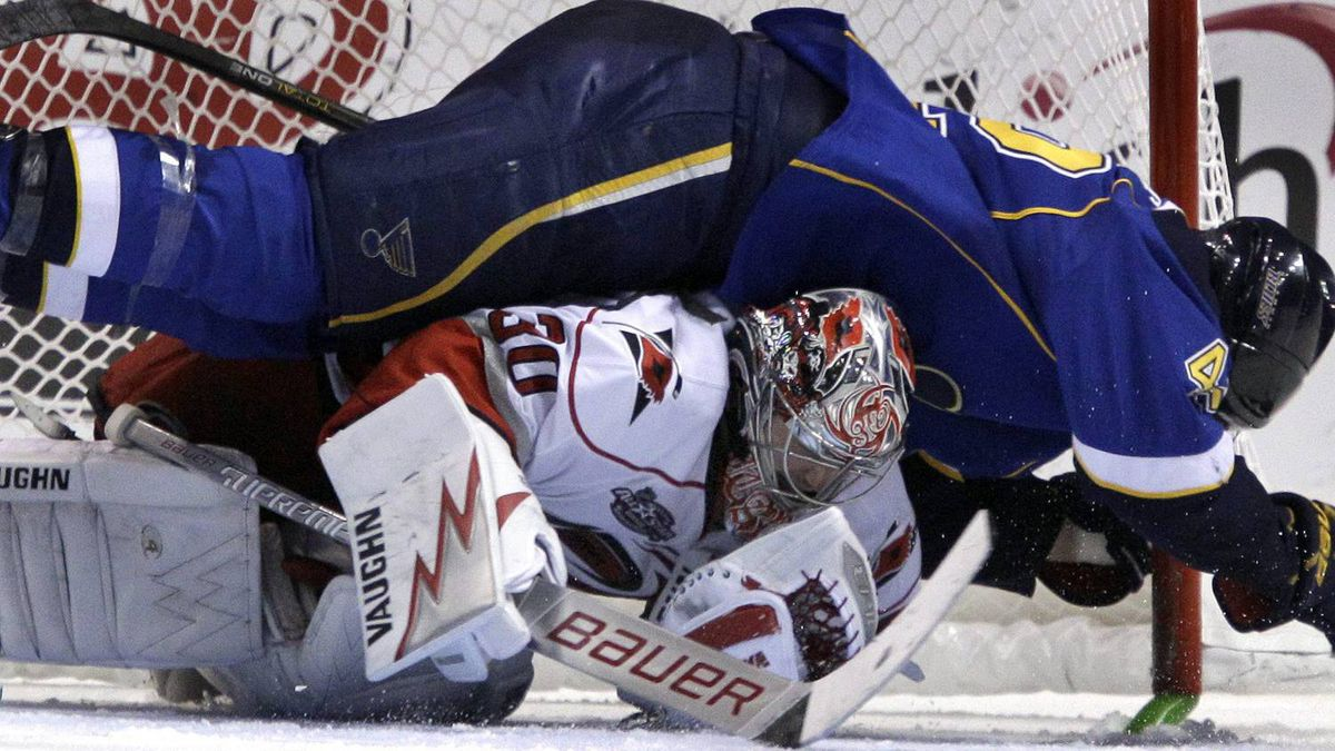 St. Louis Blues' David Backes, top, falls over Carolina Hurricanes goalie Cam Ward during overtime of an NHL hockey game Saturday, Dec. 11, 2010, in St. Louis. The Hurricanes won 2-1 in a shootout. (AP Photo/Jeff Roberson)