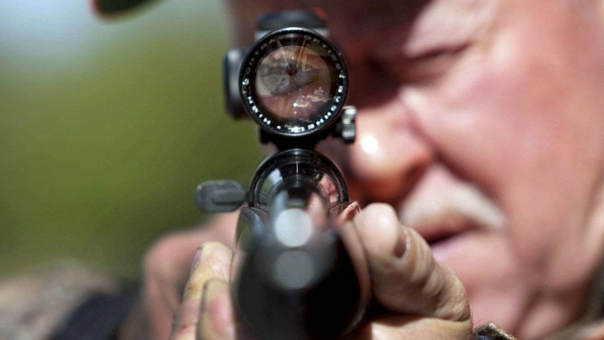A rifle owner takes aim at a hunting camp near Ottawa on Sept. 15, 2010.