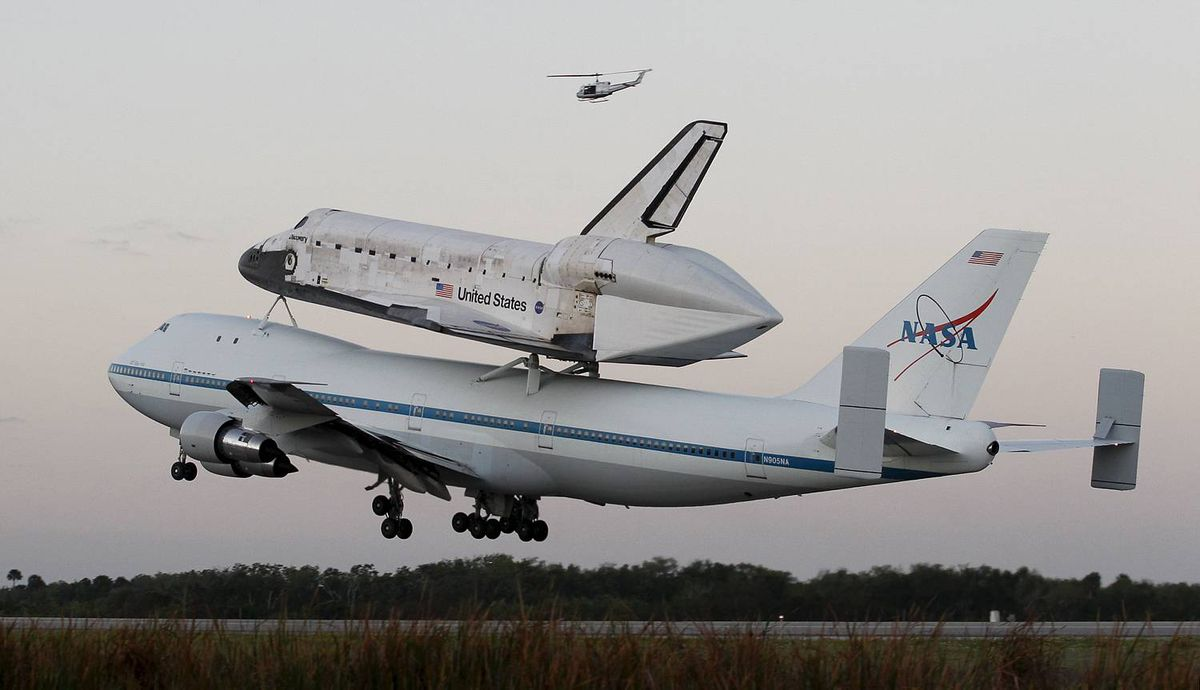 The space shuttle Discovery, attached to a modified NASA 747 aircraft, takes off in Cape Canaveral