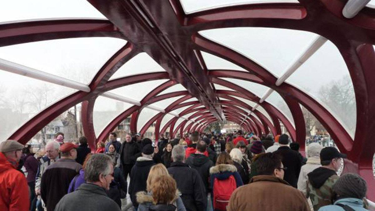Some pedestrians and cyclists wore red to celebrate the opening of the bridge. 'It's an indelible and a permanent part of the landscape of our city. It would all do us good to grow to love it,' Mayor Naheed Nenshi said.