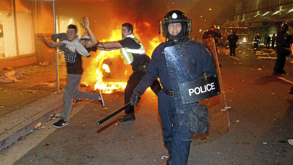 Police try to move rioters in the streets of Vancouver on Wednesday, June 15, 2011.