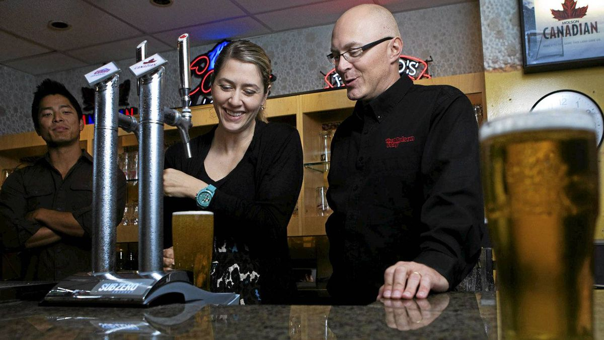 Ali Camerson receives tips on pouring beer from fellow Molson Coors employee Jeff Armstrong.