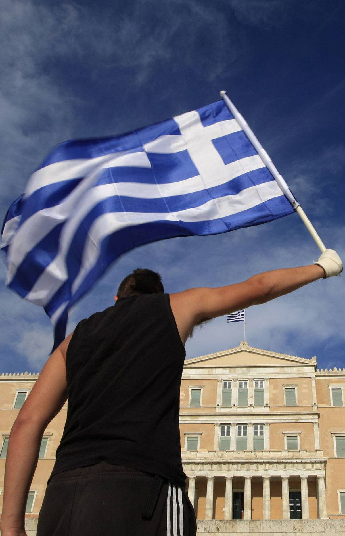 A protester raises Greek flag in front of the parliament during a rally against a new austerity package at Athens' Syntagma (Constitution) square June 11, 2011.