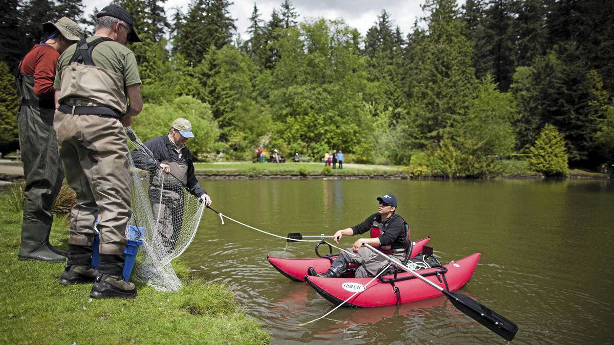 Municipal and provincial government officials prepare a fishing net to try to catch the snakehead fish in the lower pond at Central Park in Burnaby, British Columbia, Wednesday, May 23, 2012.