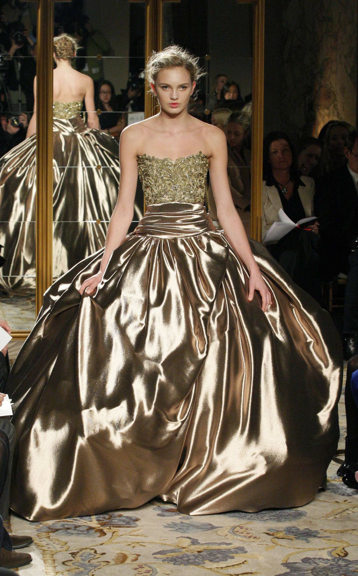 This gown could easily end up on the Oscar red carpet. Aside from the dazzling liquid gold effect of the lamé, the circumference of the hand-draped pouf skirt would appeal to any actress requiring a large body bubble.
