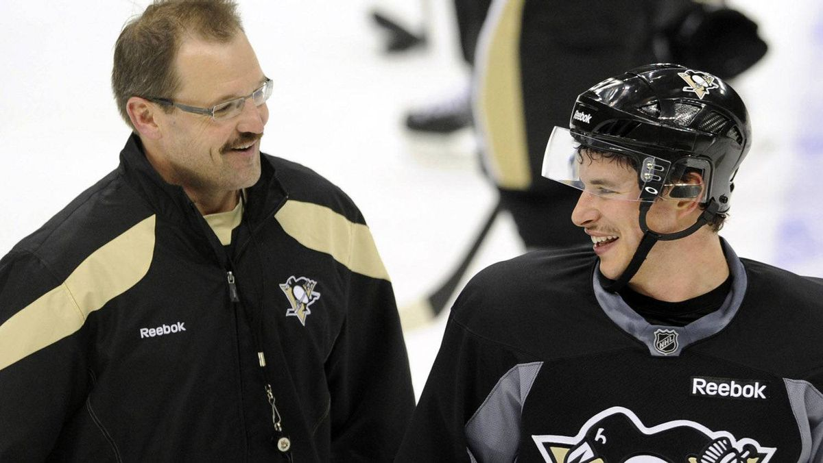 """The Pittsburgh Penguins' Sidney Crosby (R) shares a laugh with head coach Dan Bylsma during the """"morning skate"""" in preparation for his return to action Monday night against the New York Islanders in Pittsburgh, Pennsylvania, November 21, 2011. REUTERS/David DeNoma"""