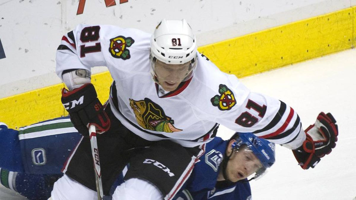 Vancouver Canucks' Jannik Hansen falls to the ice while chasing Chicago Blackhawks' Marian Hossa during the first period of their NHL hockey game in Vancouver on Wednesday.