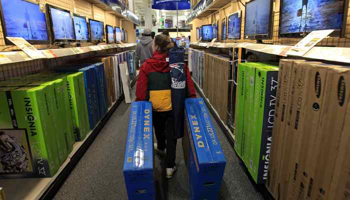 "A shopper drags boxes of televisions through the aisles at Best Buy on the shopping day dubbed ""Black Friday"" in Framingham, Massachusetts November 24, 2011."