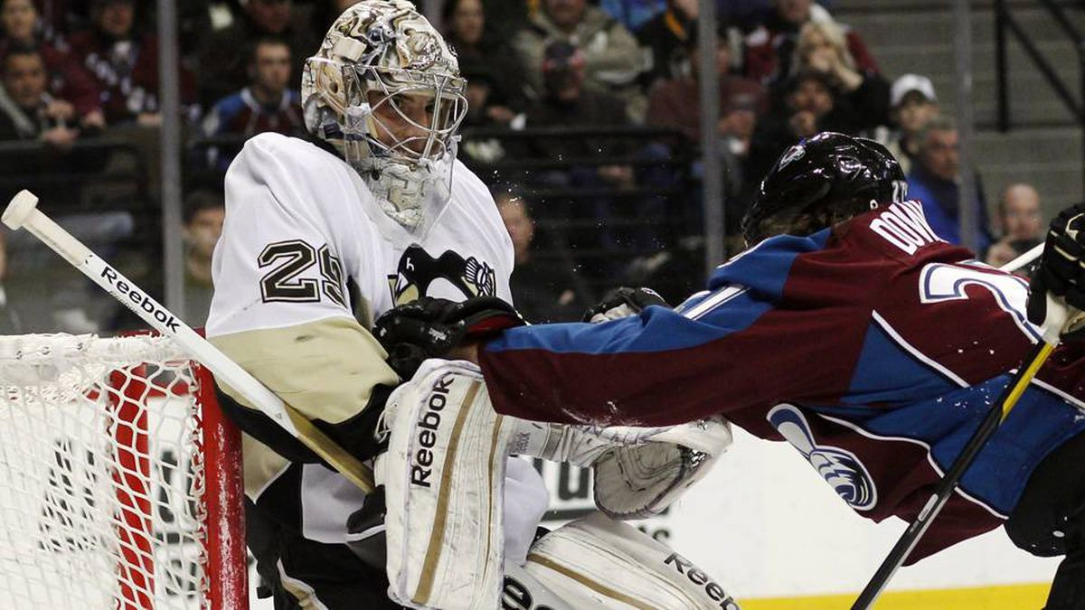 Pittsburgh Penguins goalie Marc-Andre Fleury, left, falls back against the crossbar of the net as he is pushed by Colorado Avalanche right winger Steve Downie in the third period of the Penguins' 5-1 victory in an NHL hockey game in Denver on Saturday, March 3, 2012.