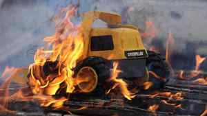 A toy Caterpillar vehicle burns in a fire on the picket lines outside Electro-Motive Canada, a subsidiary of Caterpillar in London, Ont., on Feb. 8, 2012. Caterpillar announced that it's closing the plant and moving the work to other sites in North and South America. Seven hundred workers lost their jobs.
