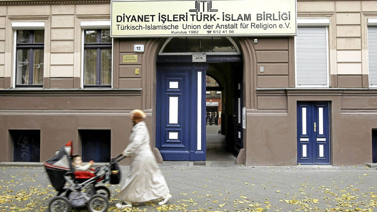 "A Muslim woman wearing a headscarf walks past a Turkish religious organization called the ""Turkish-Islamic Union Institute for Religion"" in Berlin's immigrant-heavy district of Kreuzberg on Sept. 21, 2010."