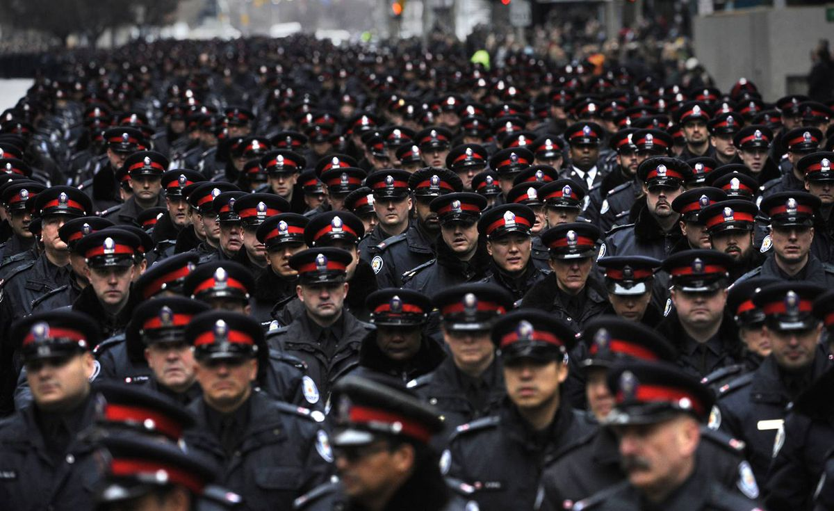Thousands of police from various police forces make their way down University Avenue as they make their way from 52 Division to the Metro Toronto Convention Centre for funeral services for Sergeant Ryan Russell on January 18 2011.