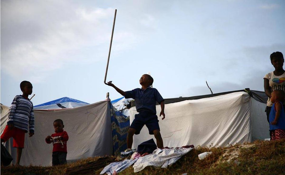 A boy balances a stick at a displaced persons' camp at Port- au-Prince's only golf course.