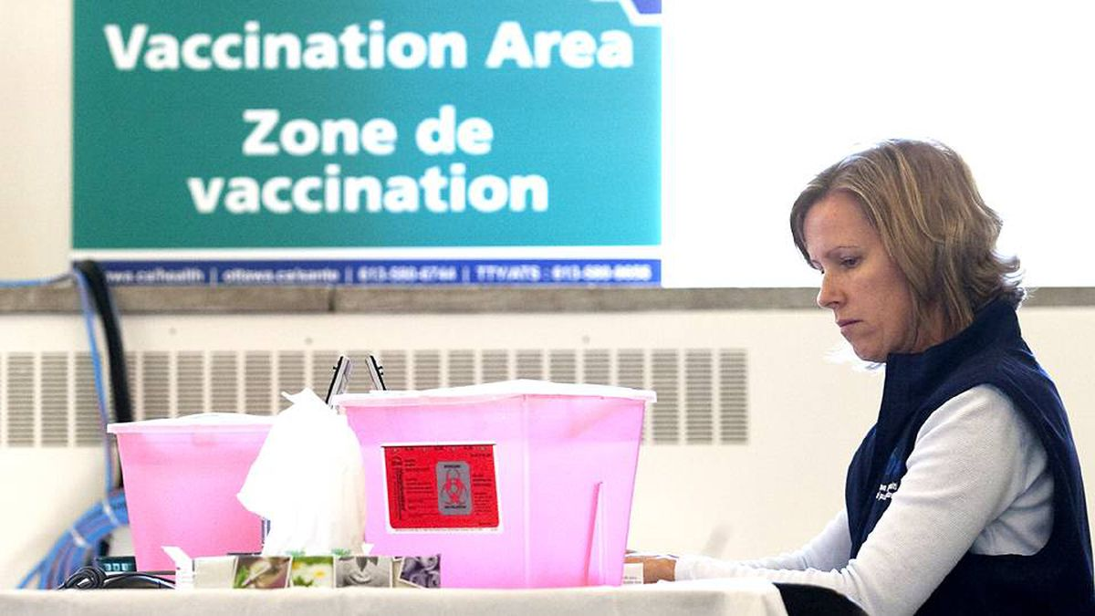 Registered practical nurse Kristen Zaine sits at a vaccine station at the Richelieu-Vanier Community Centre in Ottawa on Sunday, Oct. 25.