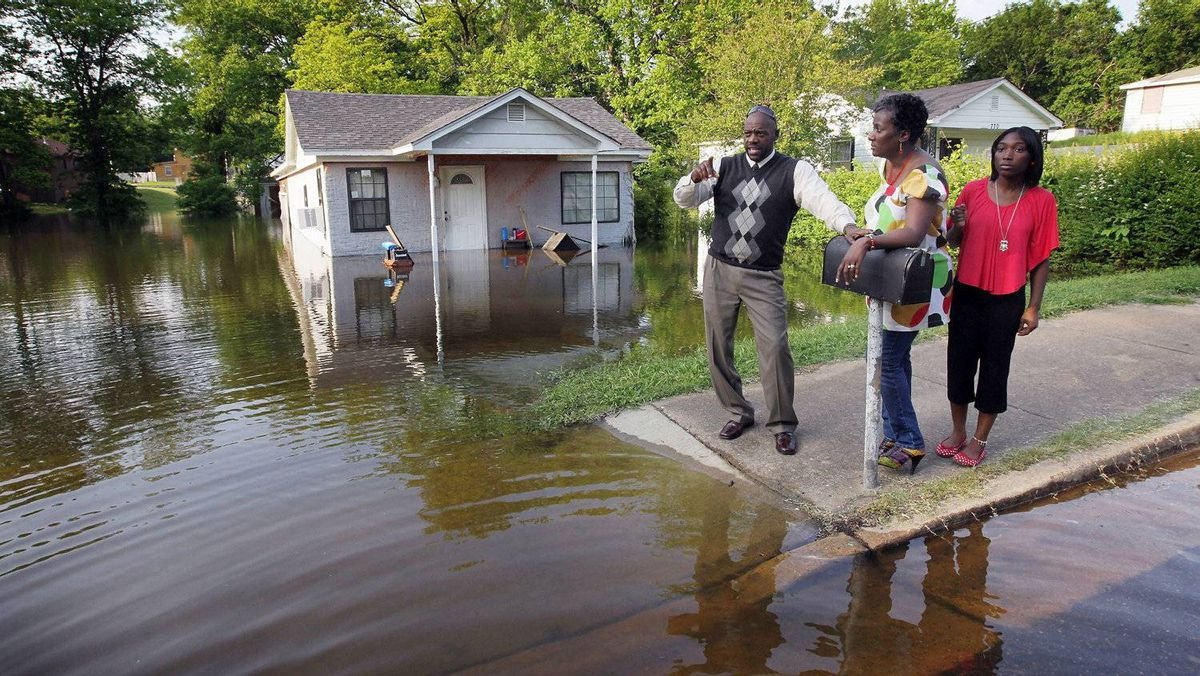 A family looks at houses being engulfed by floodwater in the West Junction neighborhood where David grew up May 8, 2011 in Memphis, Tennessee. Officials estimate about 1,300 homes are at risk of suffering dangerous flooding as the city braces for the highest Mississippi River crest since 1937.