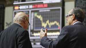 Traders stand in front of computer screens at Madrid's bourse on April 10.