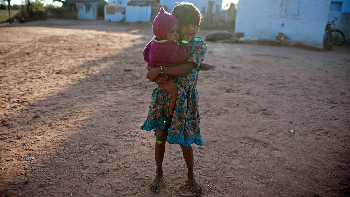 A young girl carries her sister in rural Rajasthan.