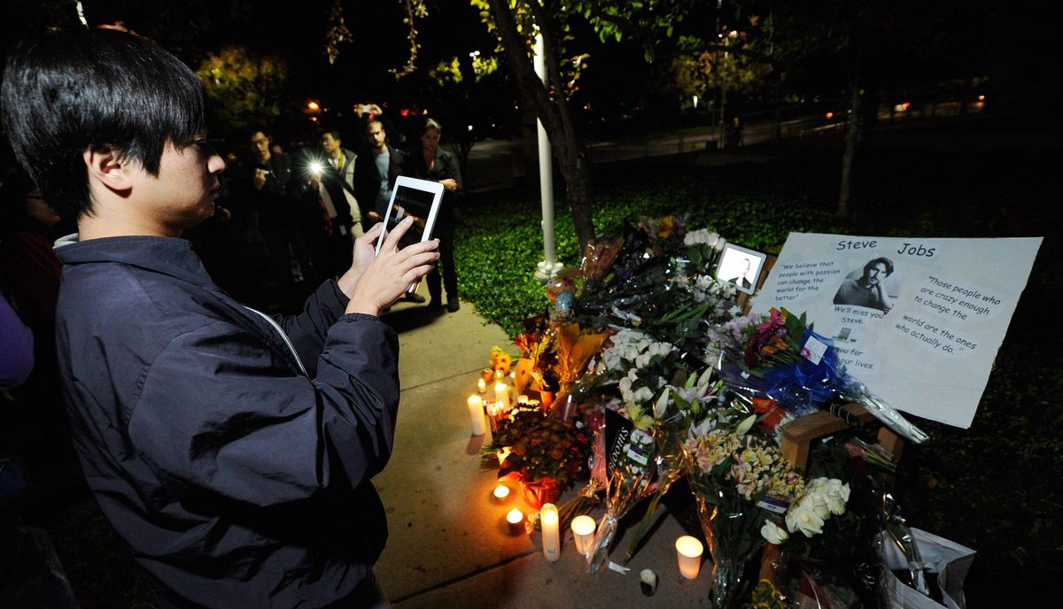 A crowd gathers at a makeshift memorial for Steve Jobs at the Apple headquarters on October 5, 2011 in Cupertino, California.