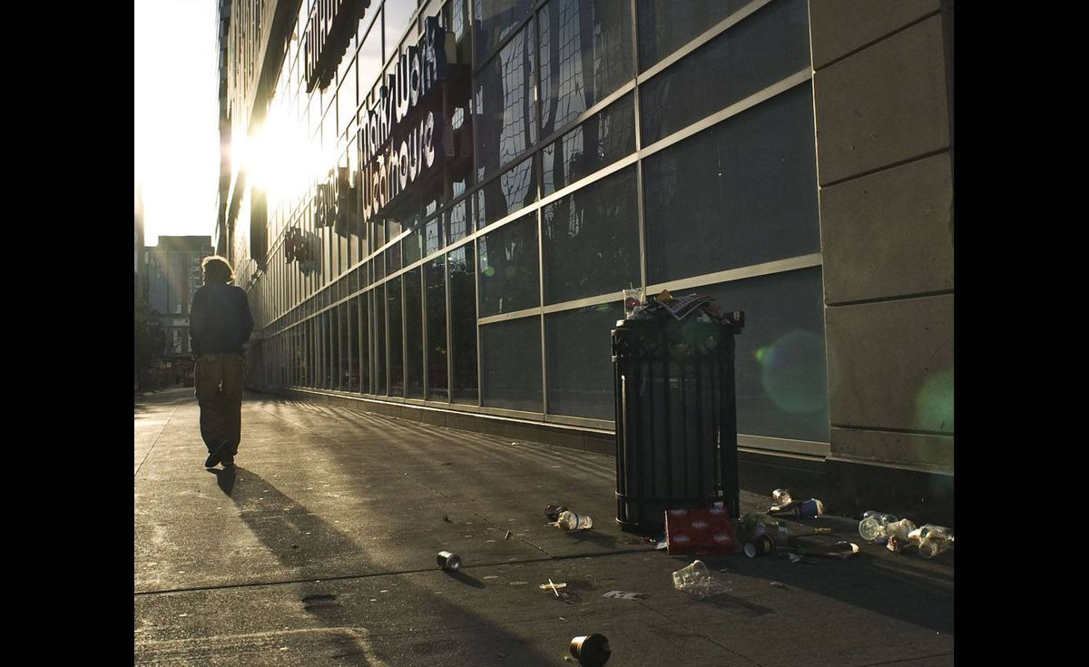 A homeless man walks into the morning sunrise past an overflowing can of garbage in Toronto on the 19th day of the 2009 civic workers strike
