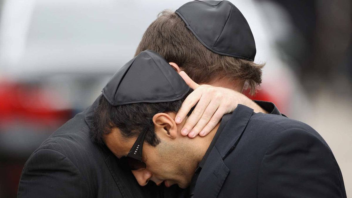 Two men embrace after the funeral service of singer Amy Winehouse at Edgwarebury Lane cemetery on July 26, 2011 in London, England.