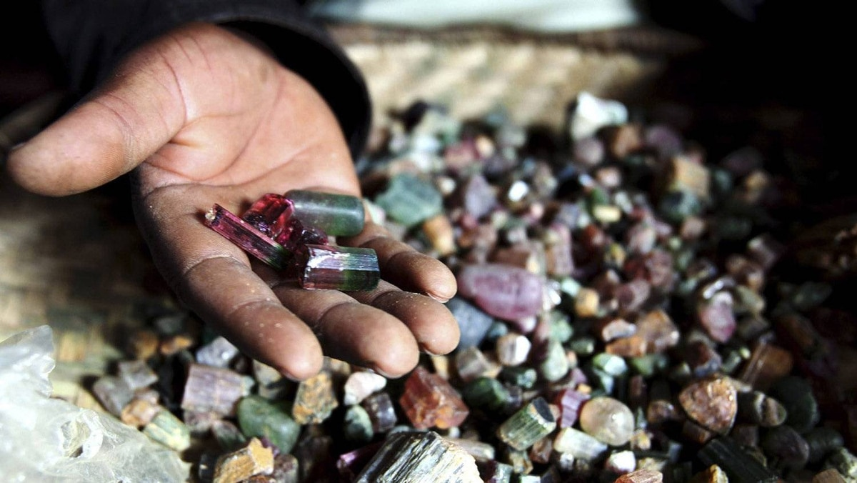 A Congolese mineral trader displays semi-precious tourmaline gem stones in a mud hut at Numbi in eastern Congo July 24, 2010. Efforts to clamp down on Congo's armed groups that finance their existence with minerals sourced from the country's conflict-wracked east -- much of which ends up in laptops, cell phones and jewellery around the world -- have been criticised for trying to achieve the impossible and risking the livelihoods of a million people in the area who depend on mining.