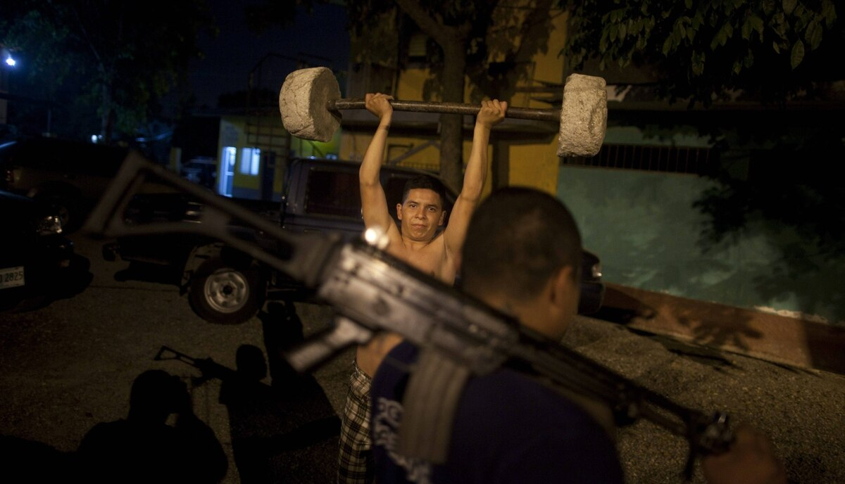 A police officer lifts weights made with concrete at a police station in San Pedro Sula, Honduras March 8, 2012.