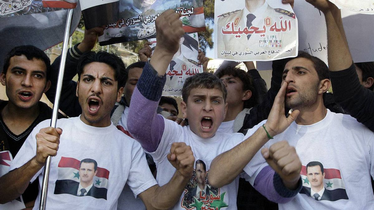 Protesters shout slogans as they carry pictures of Syrian President Bashar Assad and Syrian flags during a demonstration in front of the Russian Embassy in Beirut, Lebanon, Sunday, Jan. 29, 2012, to express gratitude for the Russian position in support of Syria. Russia has said it will use its Security Council veto to block any resolution threatening Syria with sanctions or lacking a clear ban on any foreign military interference.