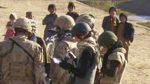Bushra Saeed, with the Department of Foreign Affairs, stands behind Calgary Herald journalist Michelle Lang as Canadian soldiers meet members of a Kuchi settlement just south of Kandahar, Afghanistan, on Wed. Dec. 30, 2009.