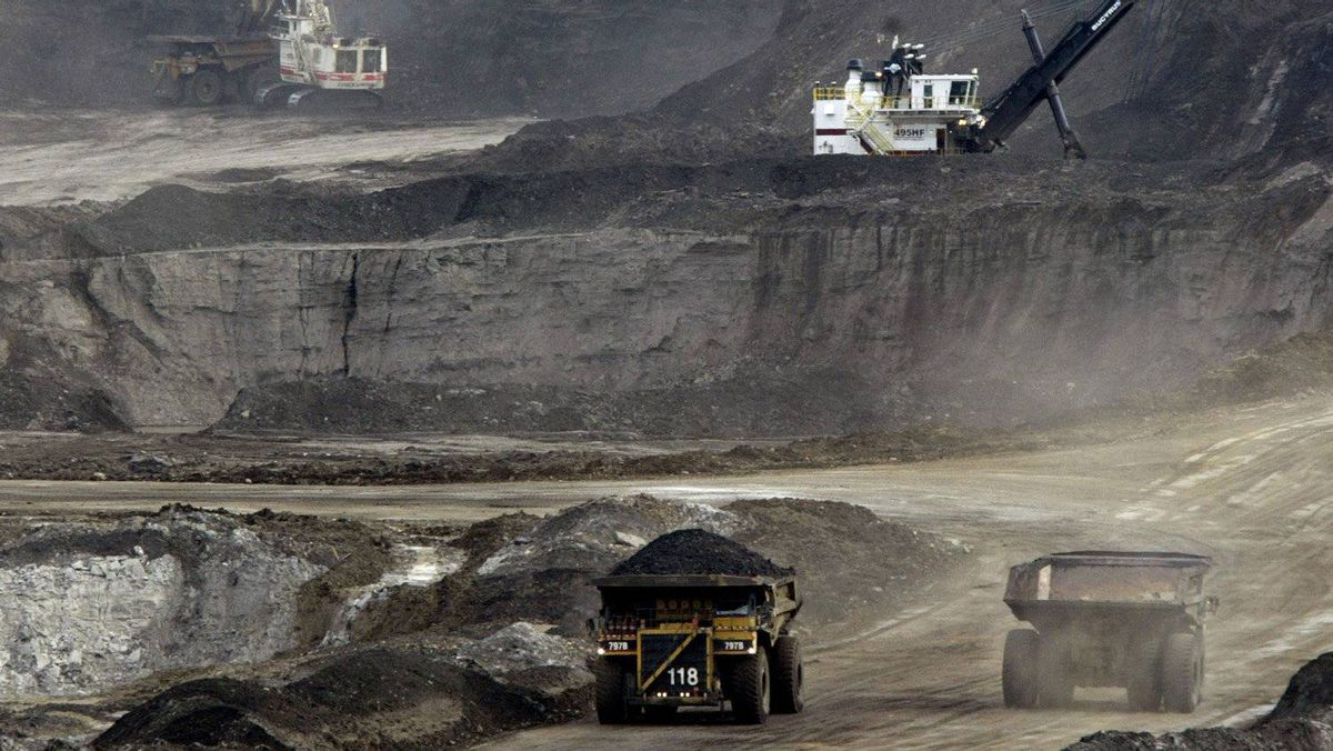 Mining trucks carry loads of oil laden sand after being loaded by huge shovels at the Albian Sands oils sands project in Ft. McMurray, Alberta in this August 5, 2005 file photo.