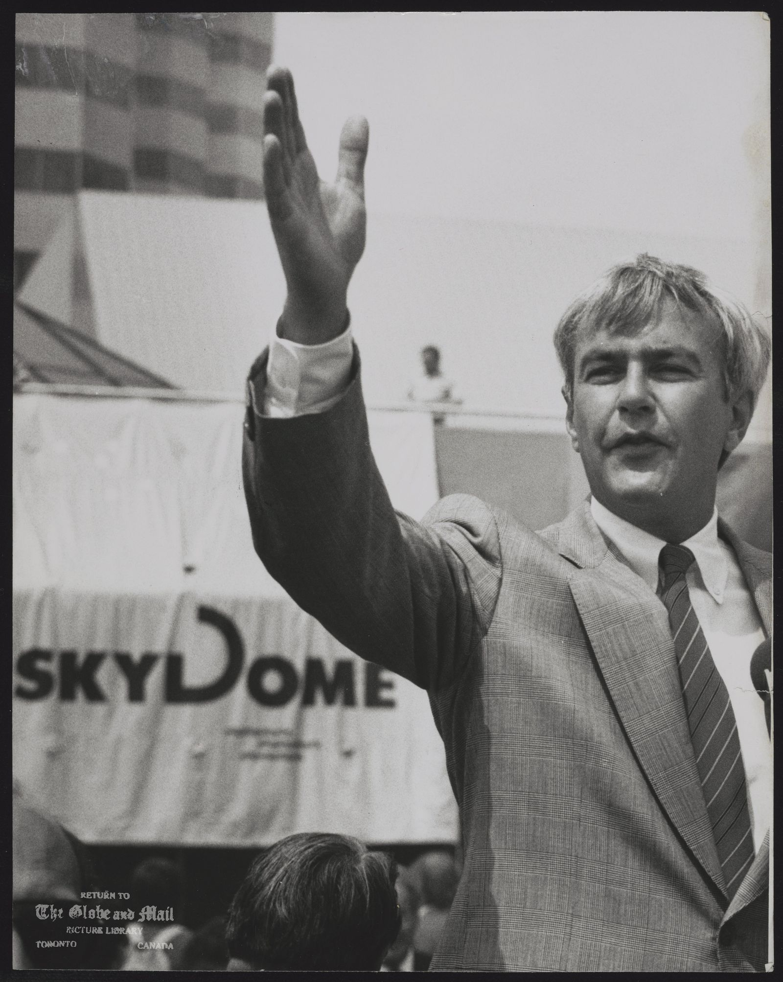 The notes transcribed from the back of this photograph are as follows: SKYDOME (Toronto) Premier David Peterson waves to onlookers yesterday during naming of the Skydome