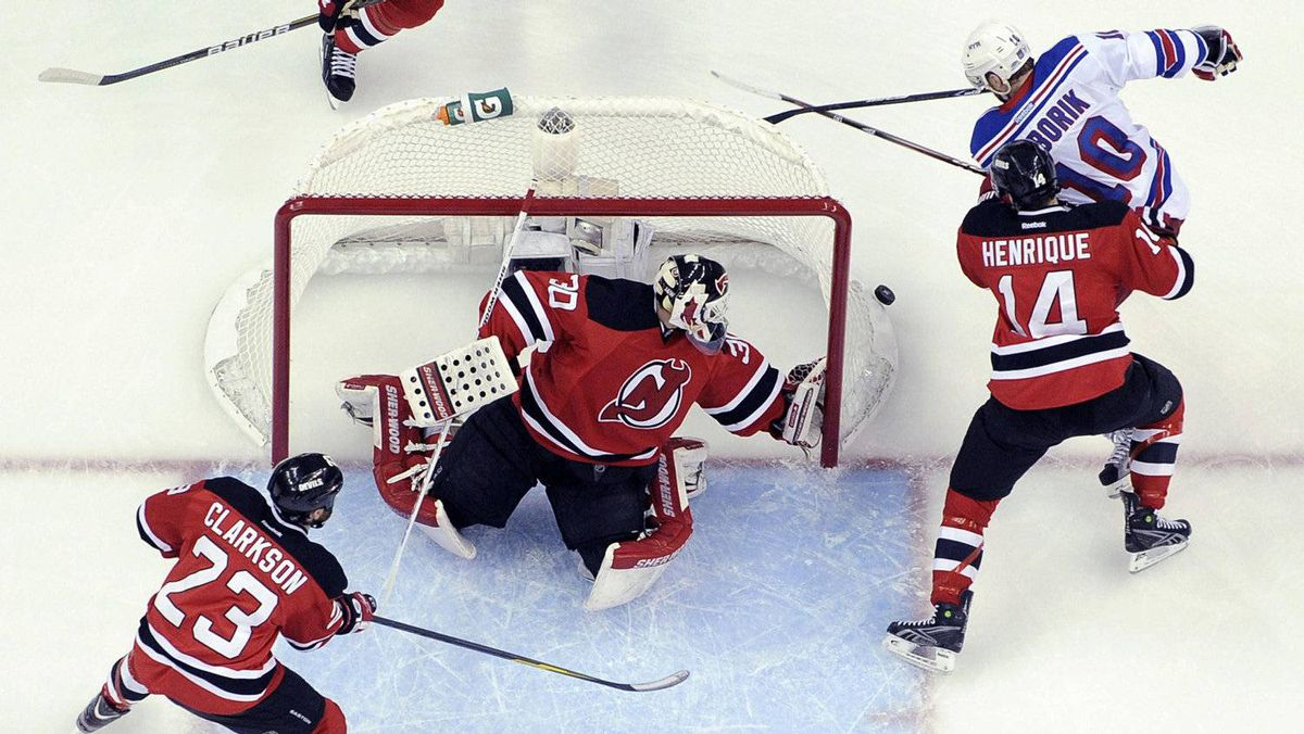 New Jersey Devils goalie Martin Brodeur (C) makes a save on New York Rangers' Marian Gaborik (10) as he is checked by New Jersey Devils' Adam Henrique (14) during the second period in Game 3 of their NHL Eastern Conference Final hockey playoff game in Newark, New Jersey, May 19, 2012.