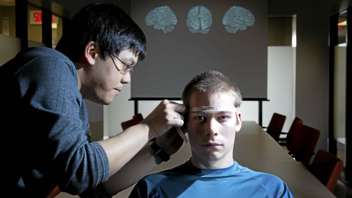 Researcher Danny Nguyen measures the head of research assistant Carl Tremblay-Cadorette, who has Asperger's syndrome, at a Montreal hospital on Wednesday.