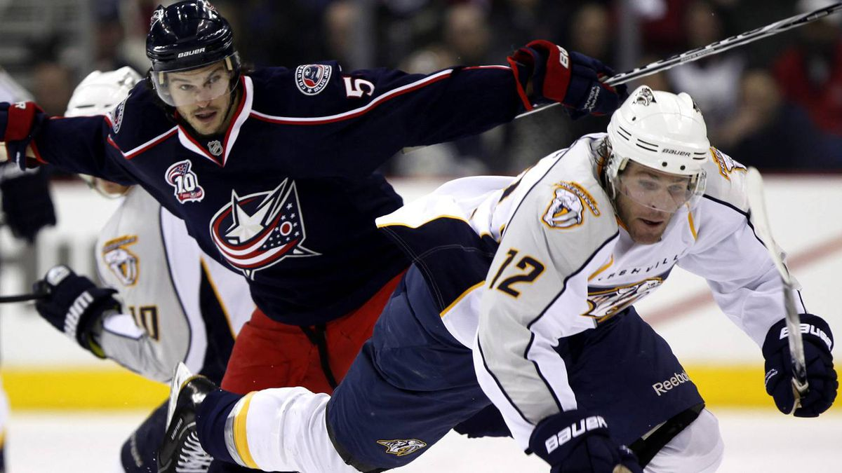 Nashville Predators' Mike Fisher (12) collides with Columbus Blue Jackets' Antoine Vernette, left, while chasing after the puck during the third period of an NHL hockey game, Tuesday, Feb 22, 2011, in Columbus, Ohio. The Blue Jackets won 4-0. (AP Photo/Terry Gilliam)