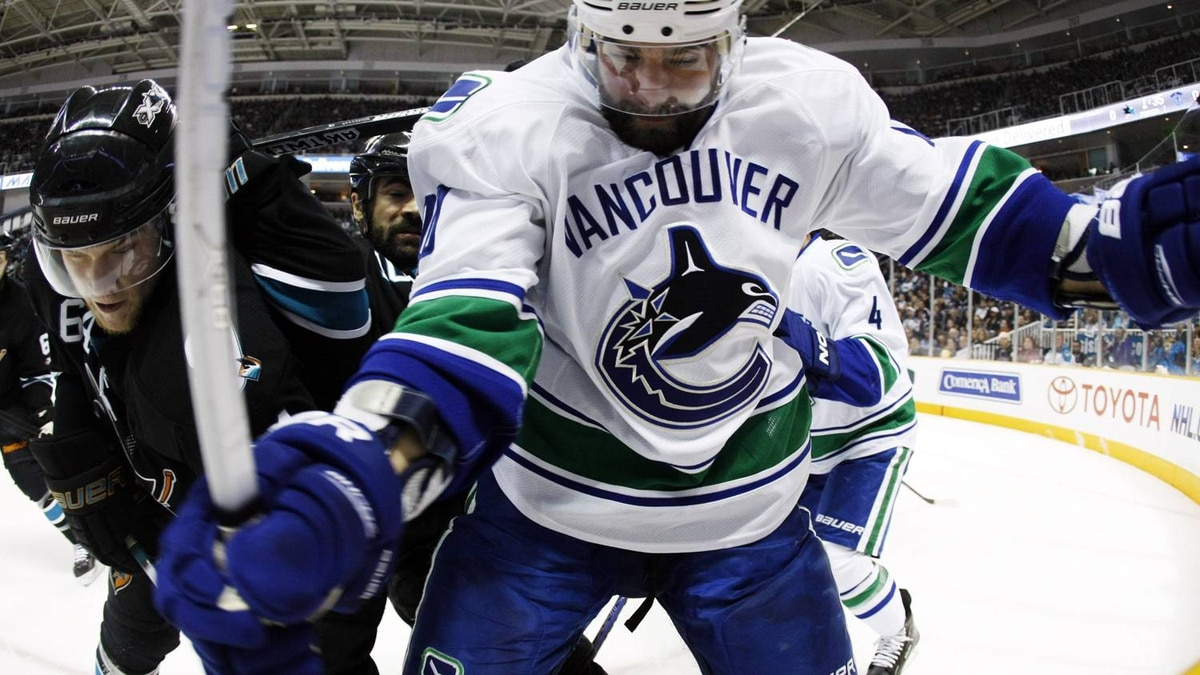 Vancouver Canucks left wing Christopher Higgins, right, collides with San Jose Sharks left wing Jamie McGinn. (AP Photo/Marcio Jose Sanchez)