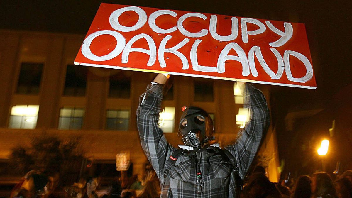 Occupy Oakland protester Melvin Kelley holds up a sign in a lot the group had planned to occupy, in Oakland, California, Nov. 19, 2011.