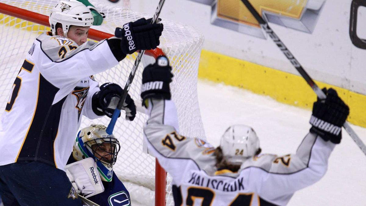 Vancouver Canucks goaltender Roberto Luongo, centre, looks on as Nashville Predators' Matt Halischuk celebrates his game winning goal with teammate Jerred Smithson during the second overtime period of game 2 of an NHL Western Conference semi-final Stanley Cup playoff hockey series in Vancouver, B.C., on Saturday, April 30, 2011.