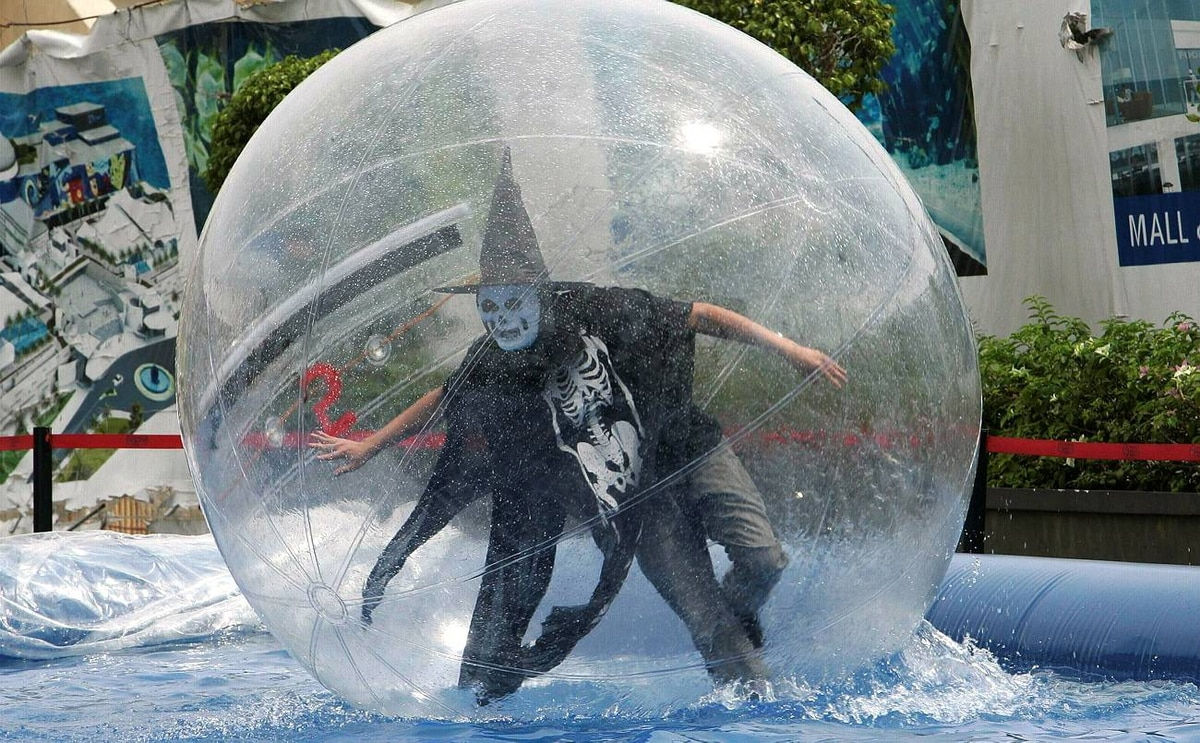 A worker wearing a Halloween costume rides in a water ball to attract customers outside the Manila Ocean Park October 30, 2009.