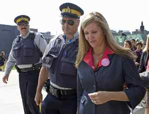 With RCMP officers keeping a throng of reporters at bay, status of women Helena Guergis leaves Parliament Hill on Sept. 17, 2009.