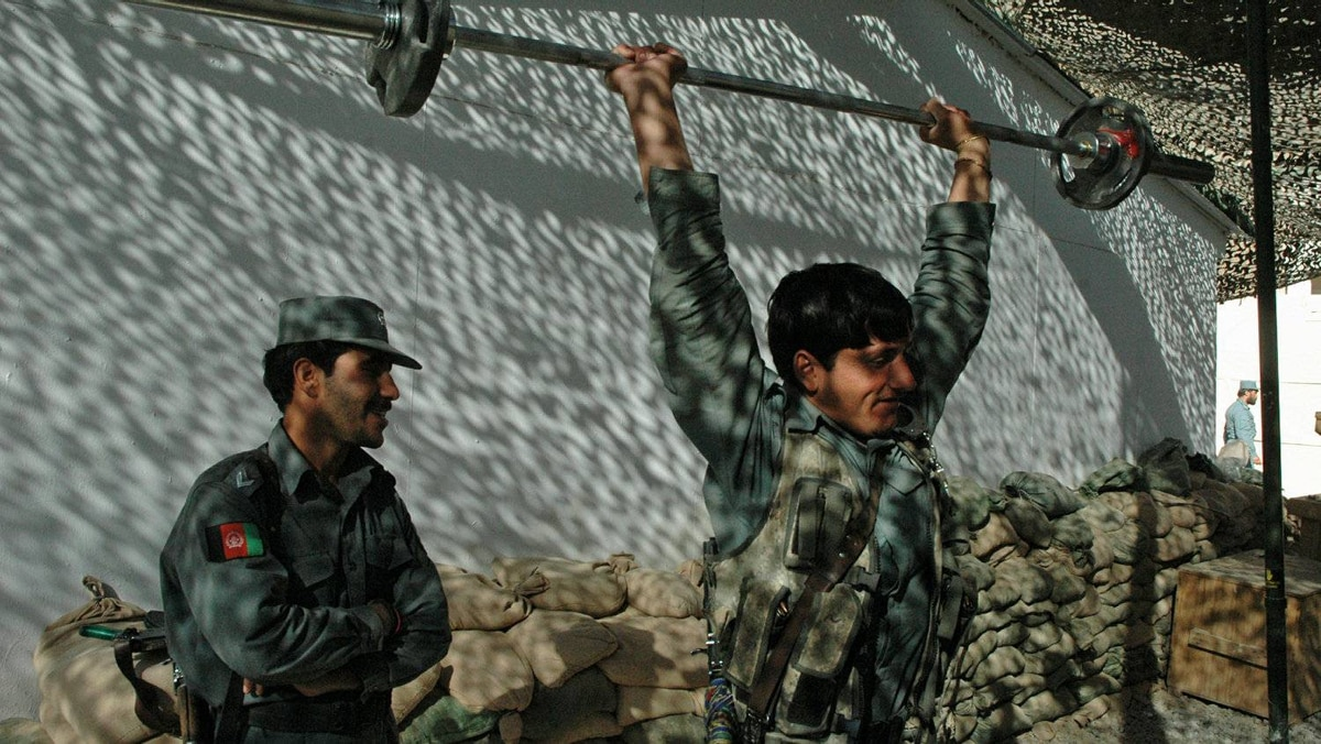 An Afghan police officer exercises during a break in training by U.S. military police in Kandahar on Nov. 12, 2010.