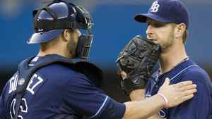 Tampa Bay Rays catcher Chris Gimenez gives pitcher Jeff Niemann a pat on the shoulder after he was hit by a grounder by Toronto Blue Jays Adam Lind during first inning AL action in Toronto on Monday May 14, 2012. THE CANADIAN PRESS/Frank Gunn
