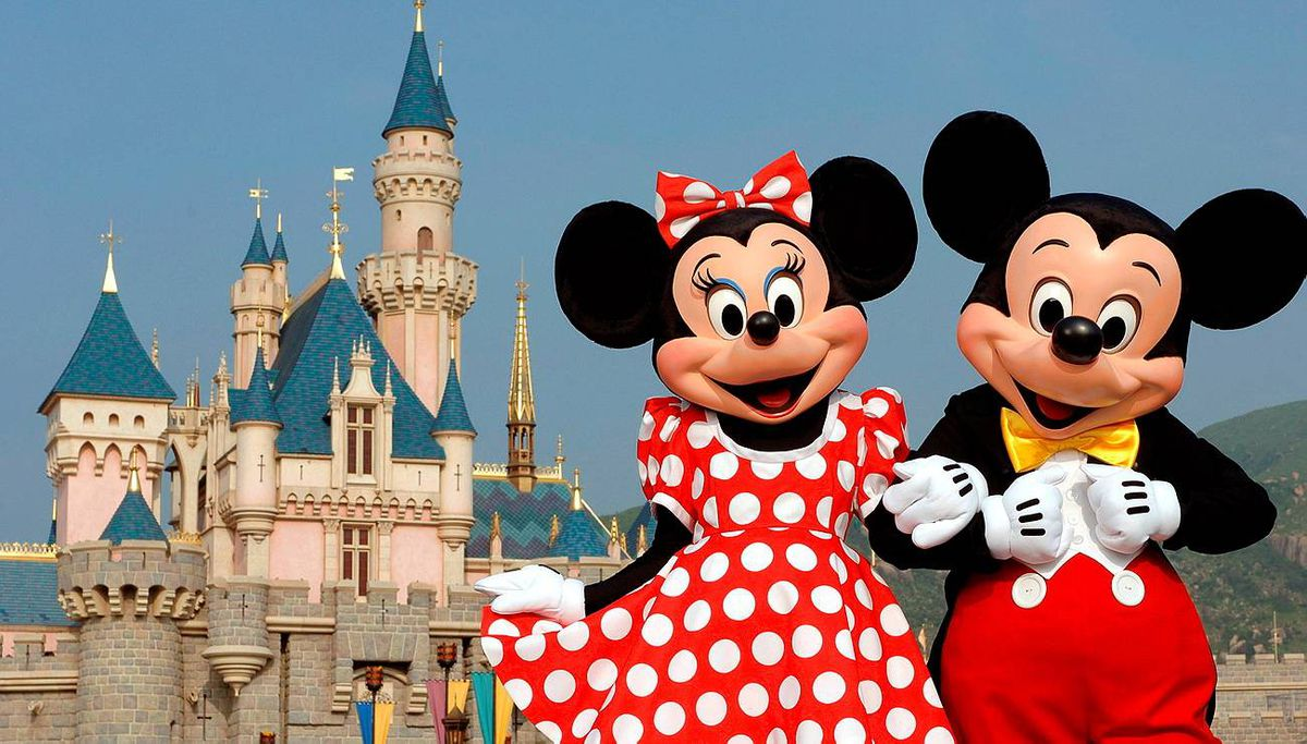 Disney characters Mickey Mouse and Minnie Mouse pose in front of the Sleeping Beauty Castle in Hong Kong's Disneyland Park. MARK ASHMAN/AP